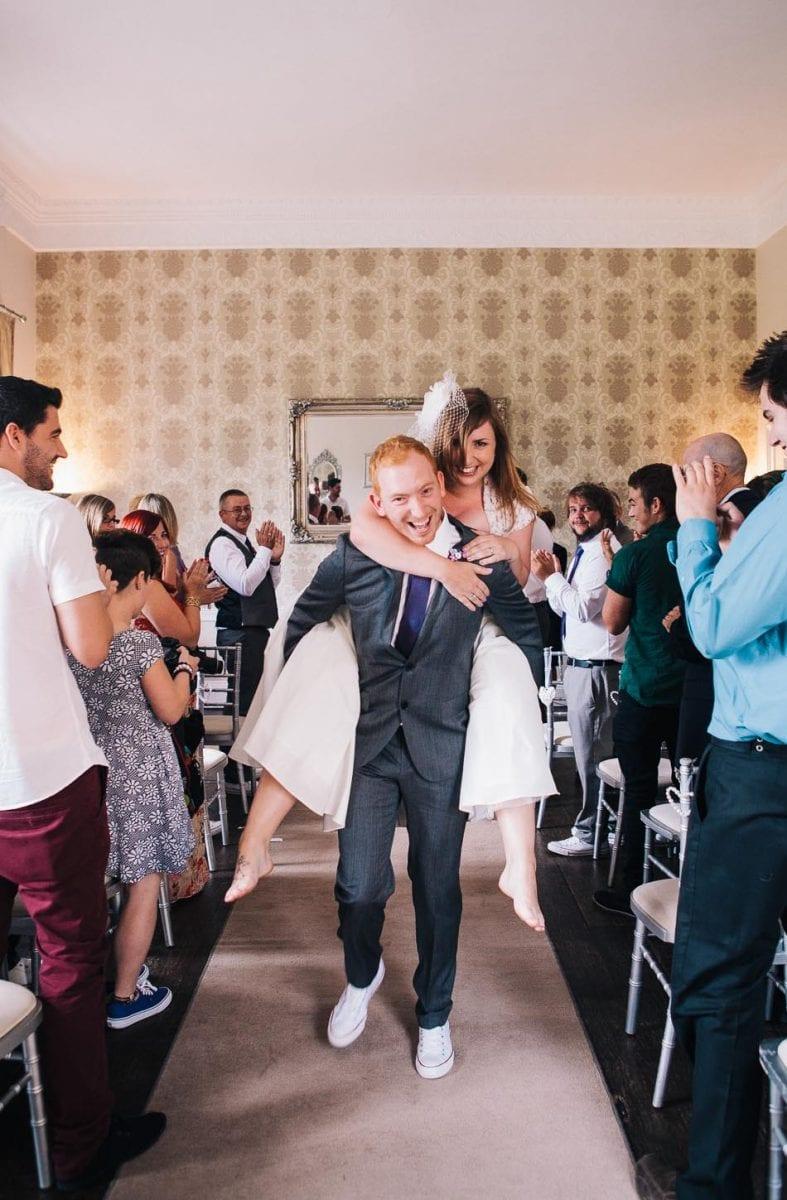 Bride getting piggyback from groom