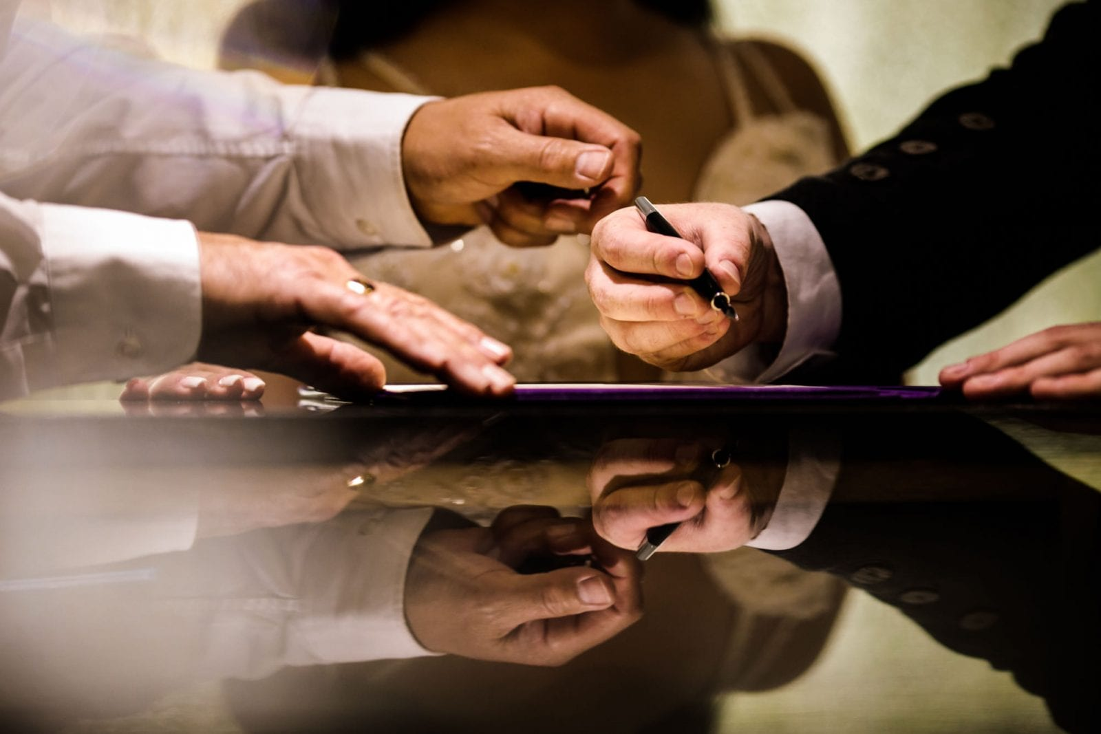 Hands signing the register at a wedding