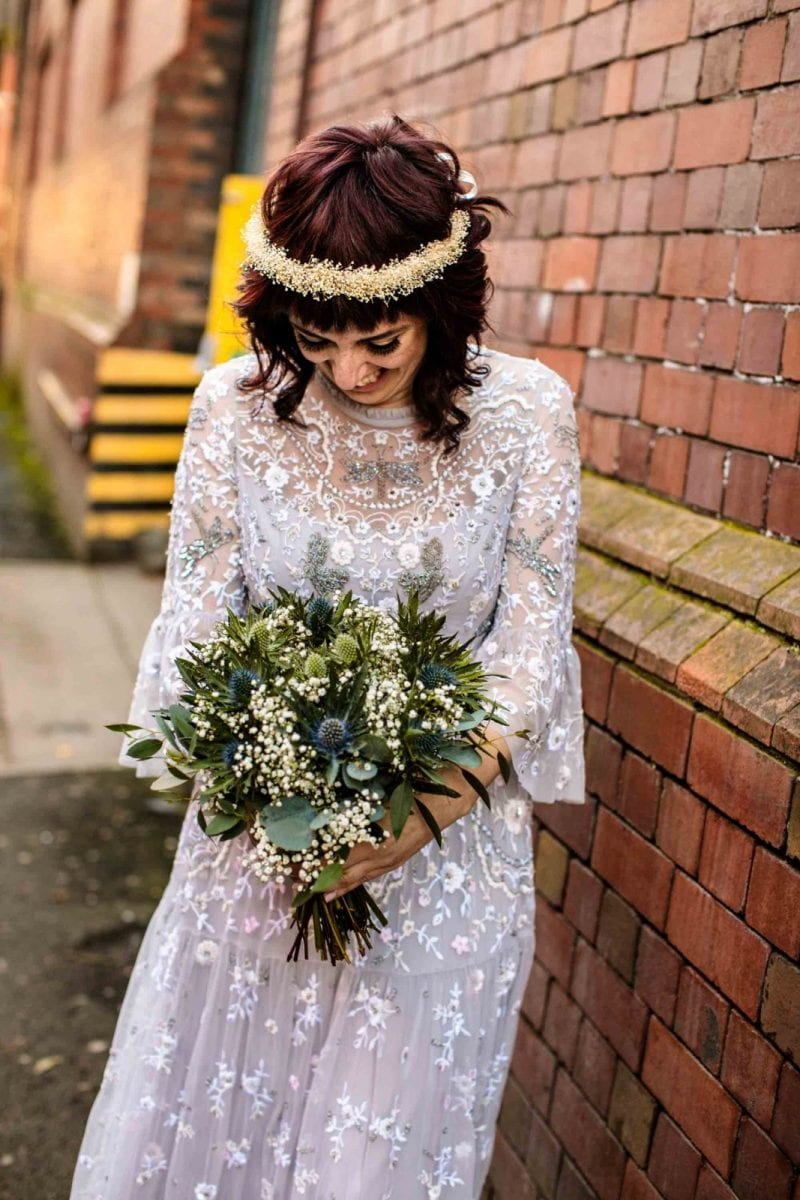 Alternative bride looking at bouquet in Needle & Thread wedding dress