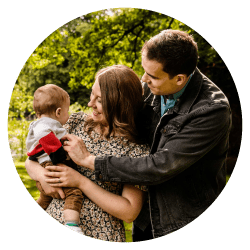 A family portrait photography cheshire session showing a woman and a man holding a baby outdoors.