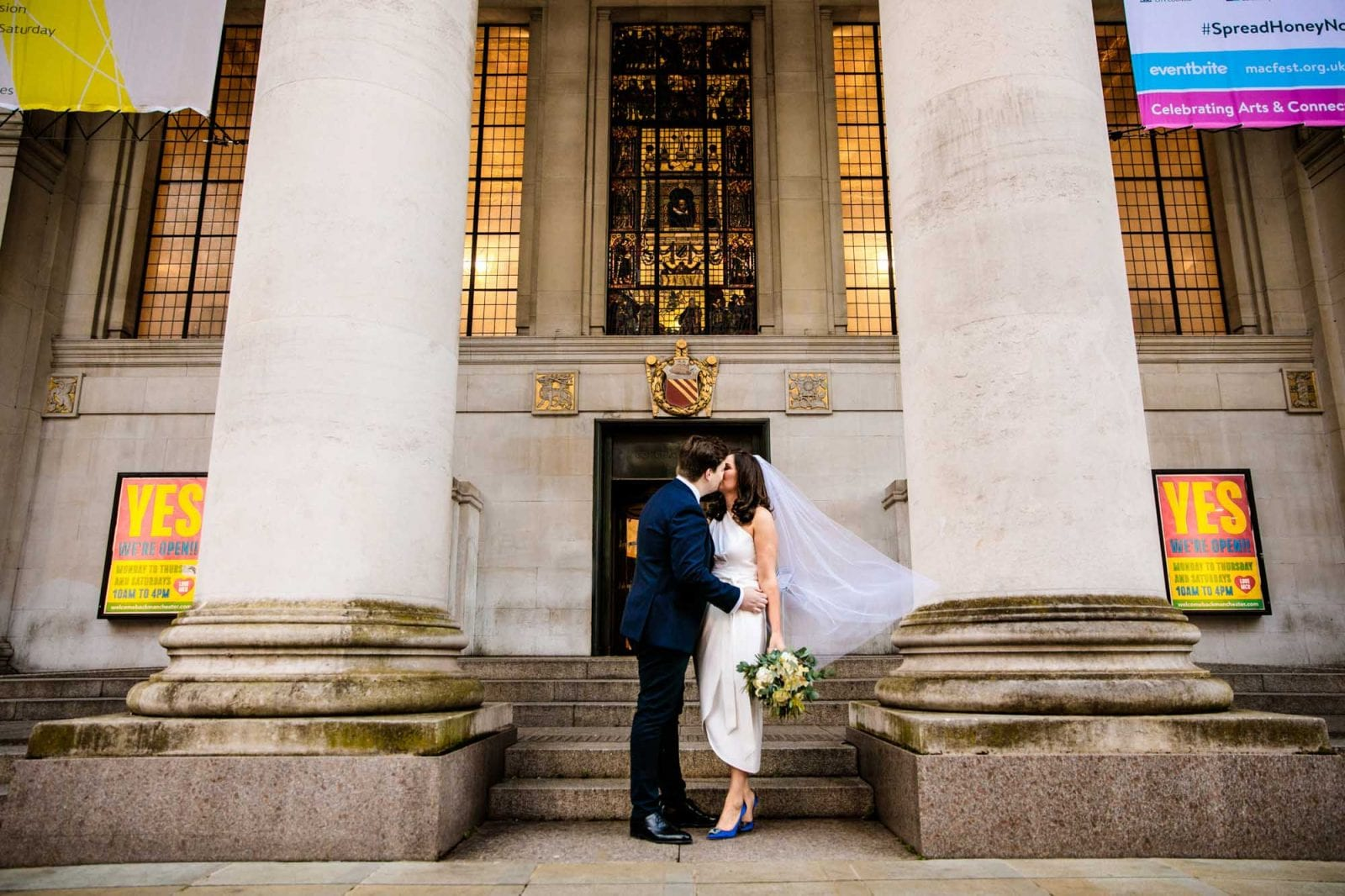 Bride and groom kissing outside Manchester Library