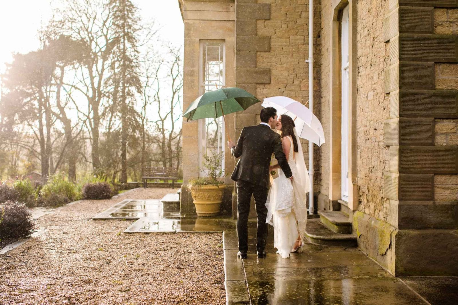 Bride and groom kissing with umbrellas at St Tewdrics House