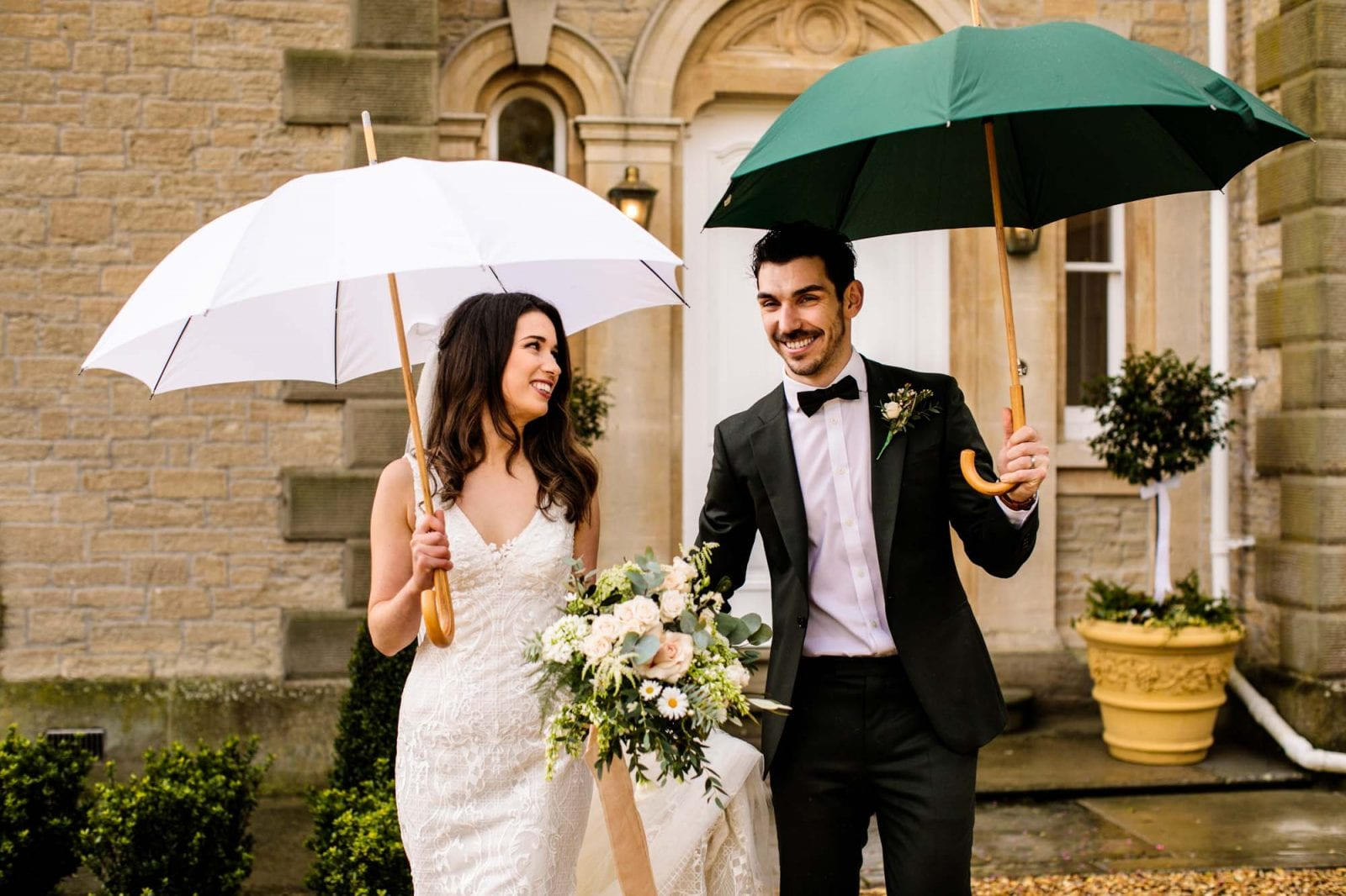 Bride and groom with umbrellas at St Tewdrics House