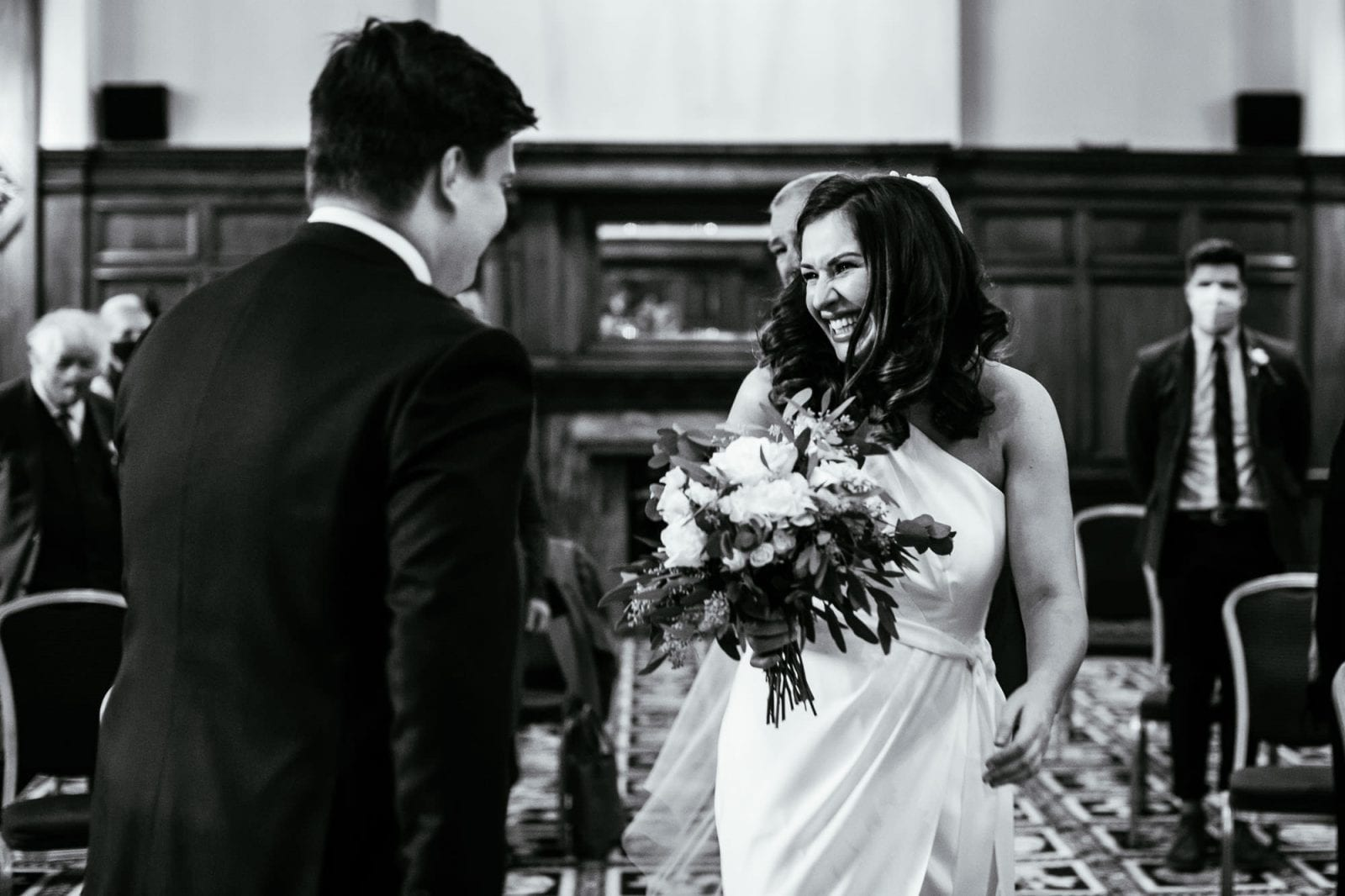 Bride smiling as she greets groom at the end of the aisle