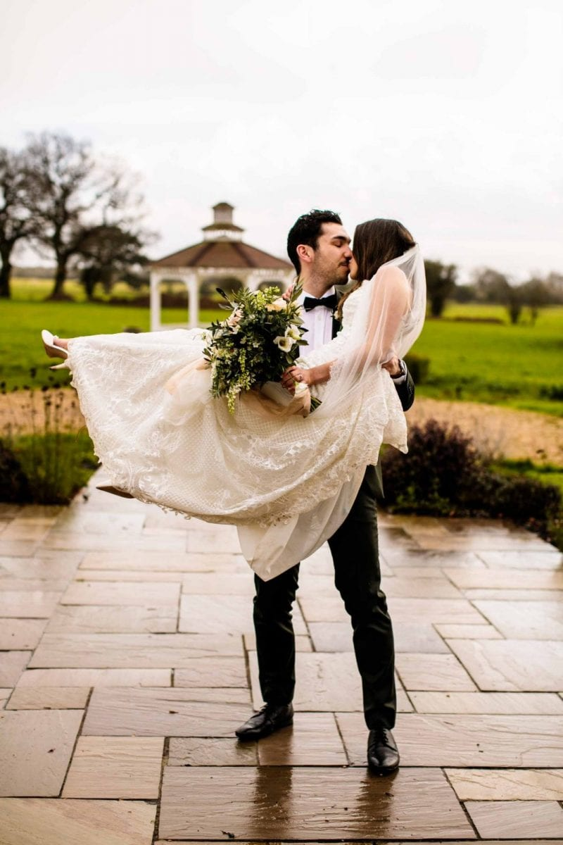 Groom lifting bride and kissing at St Tewdrics House
