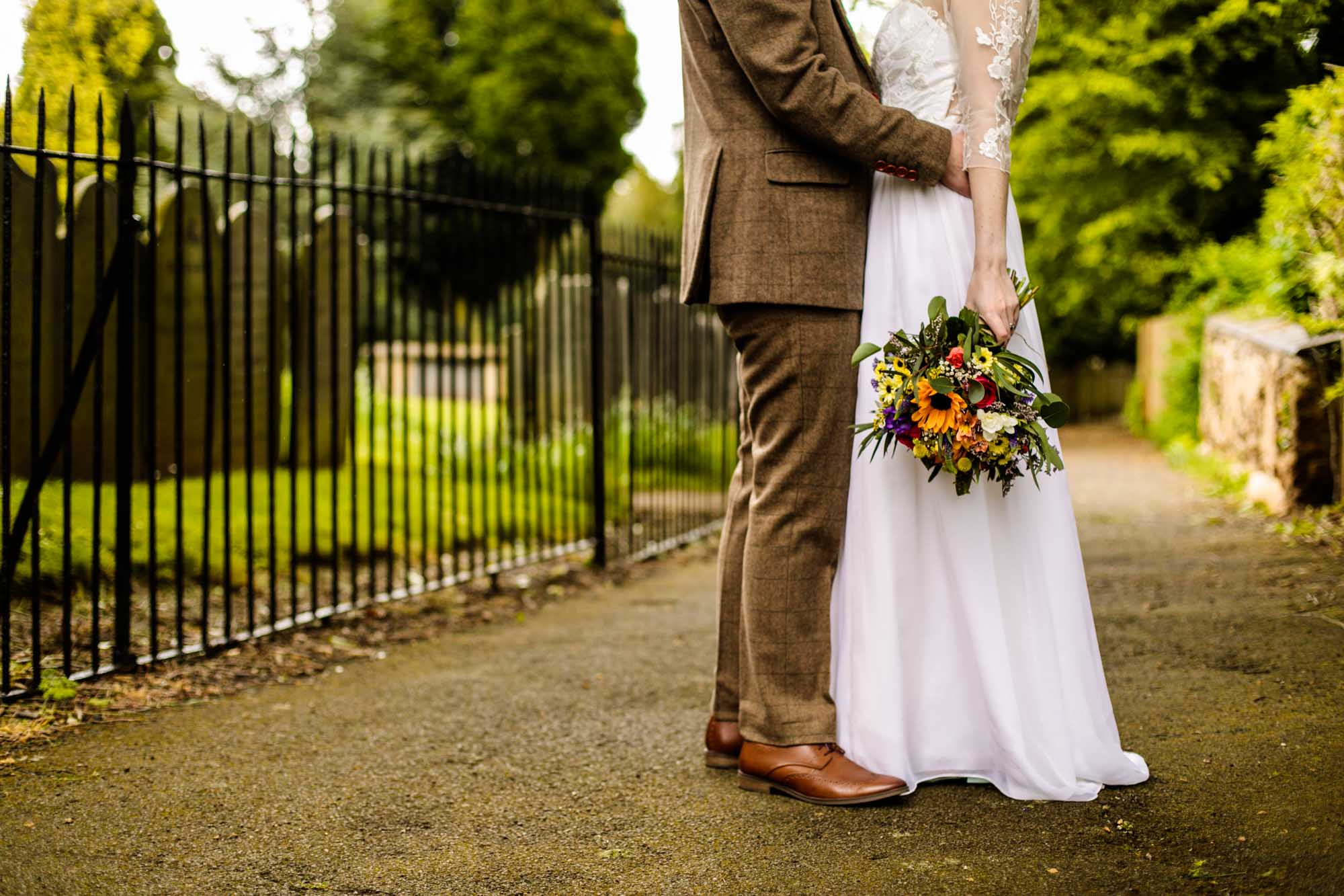 Bride and grooms feet with colourful wedding flowers