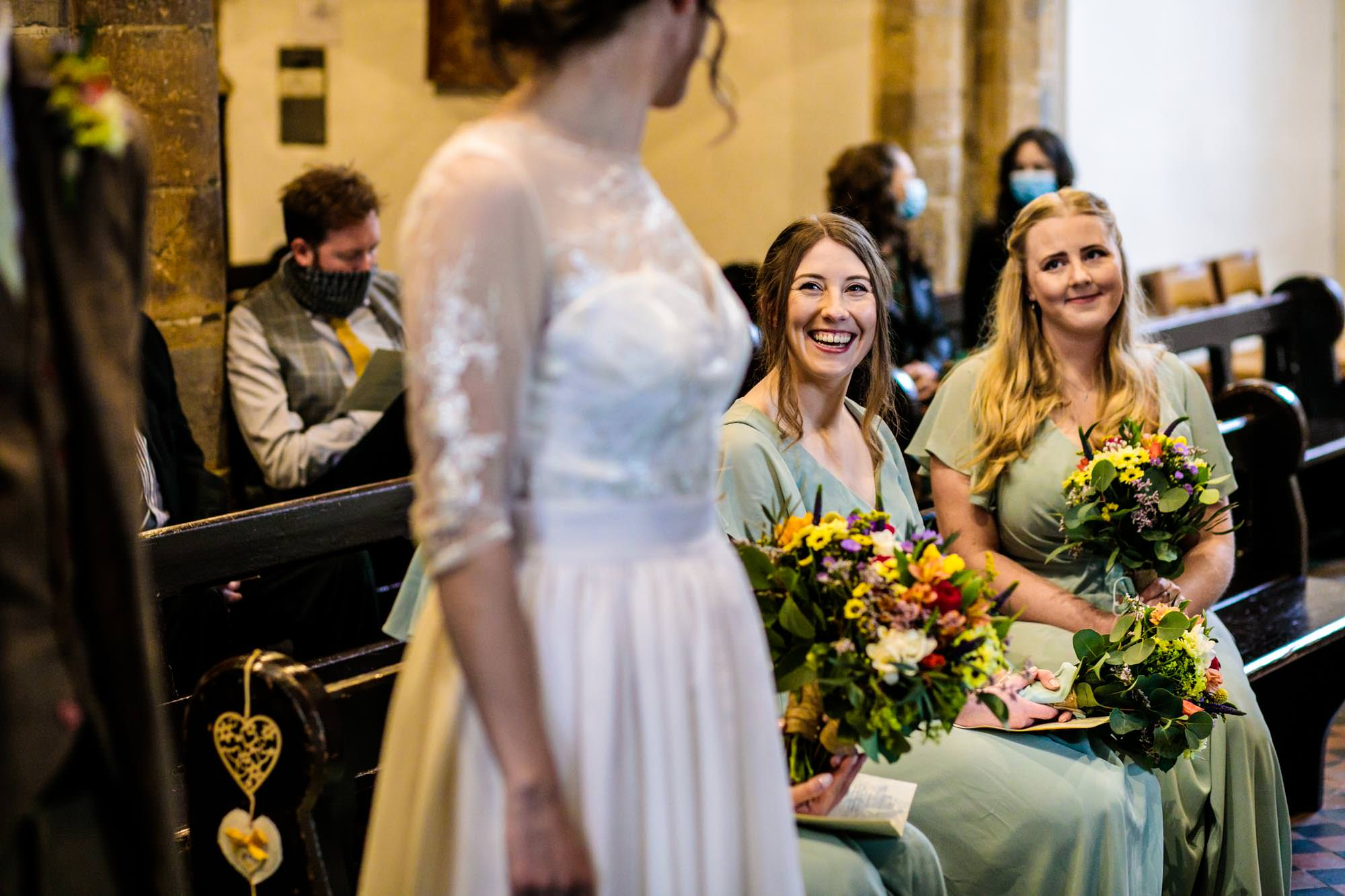 Bridesmaid smiling at bride in church