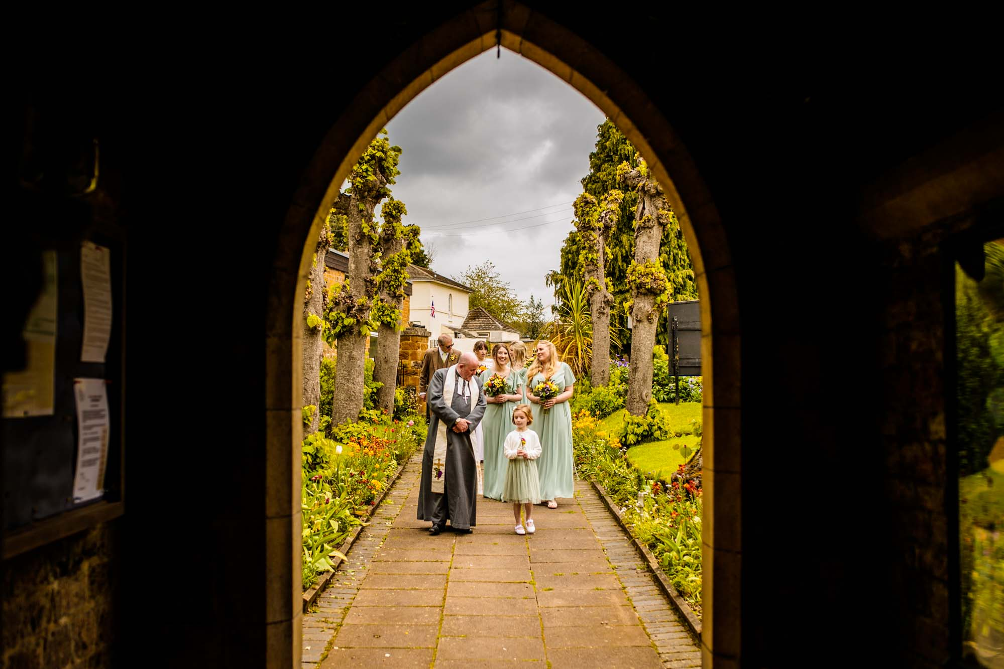 Vicar talking to flower girl entering church