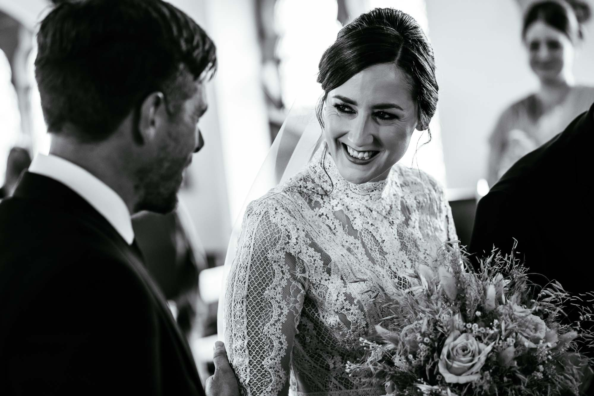 Bride smiling at groom in church