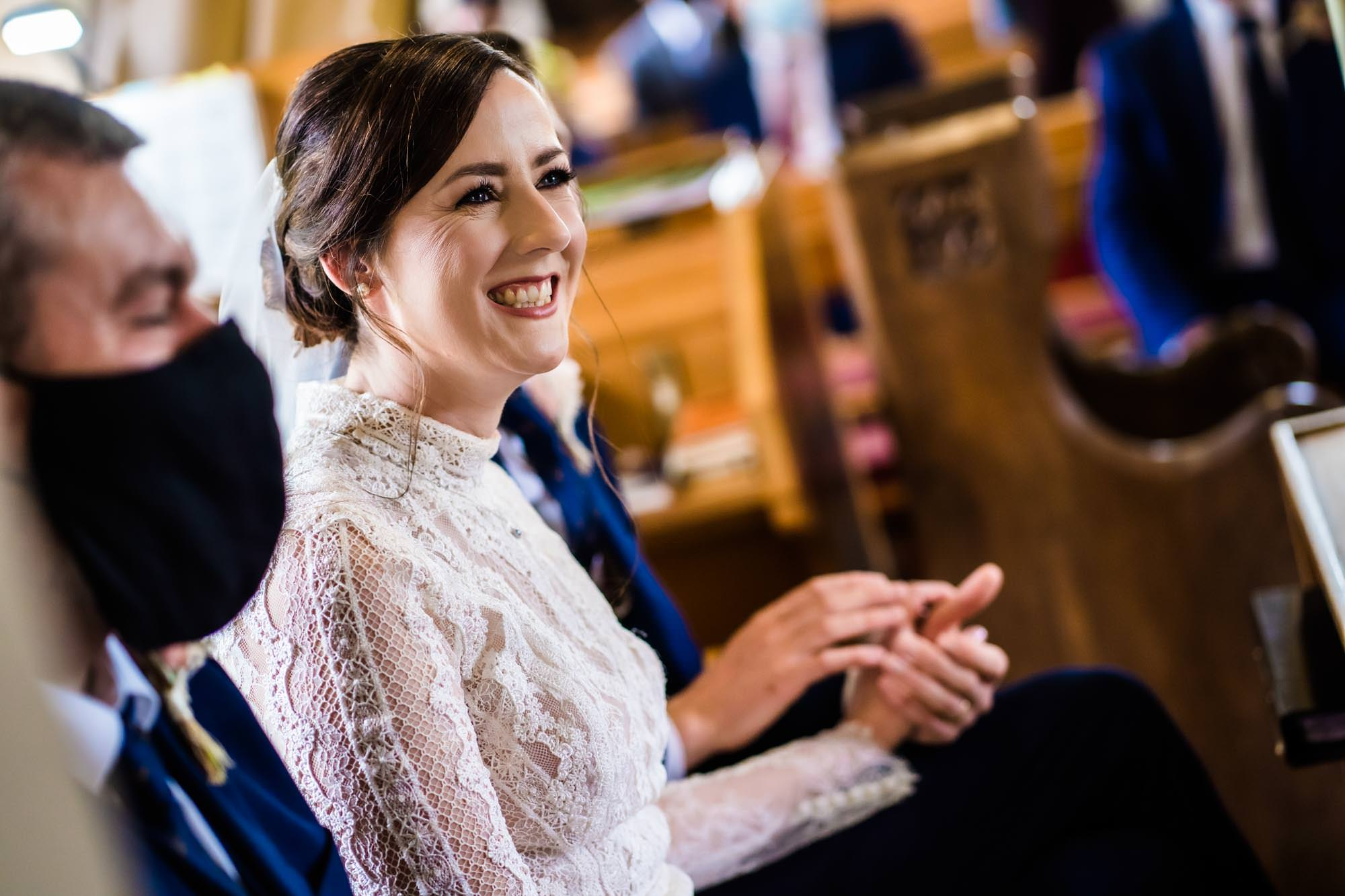 Bride smiling holding grooms hand