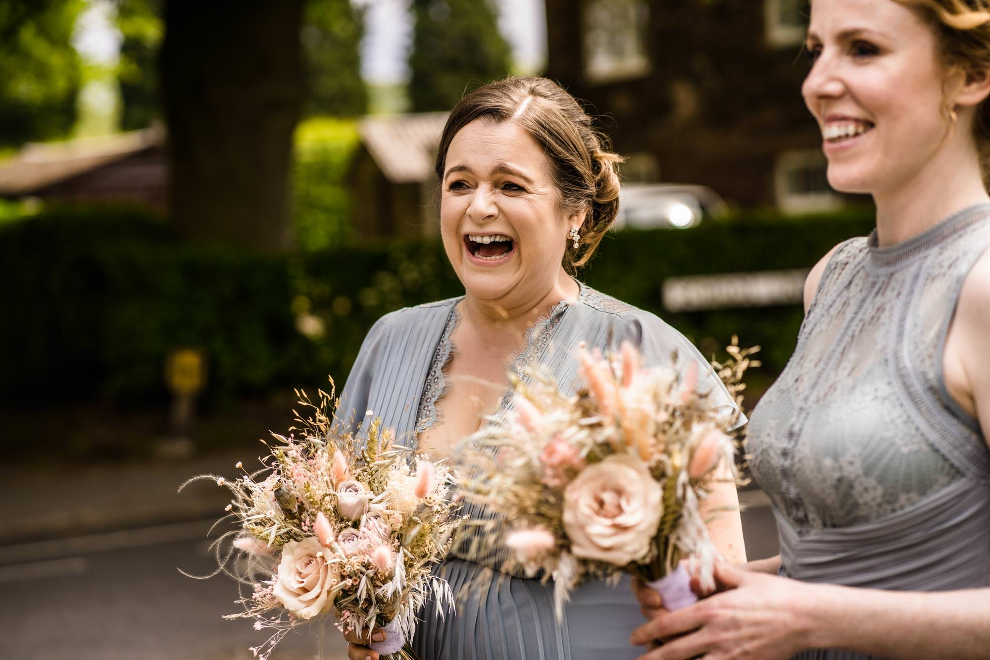 Bridesmaid laughing with wedding bouquet