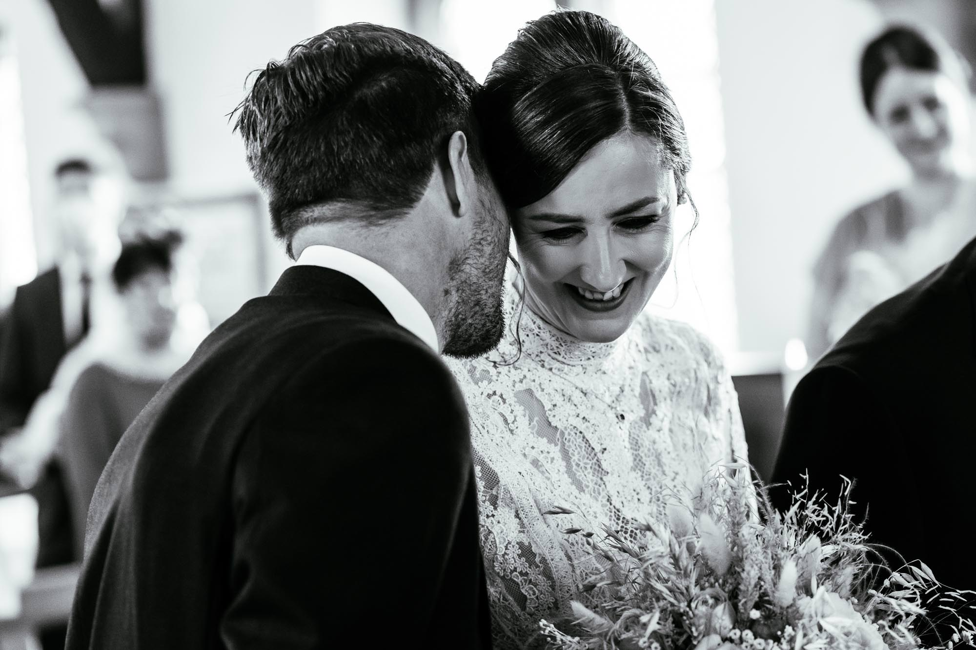 Grooms whispering to bride in church