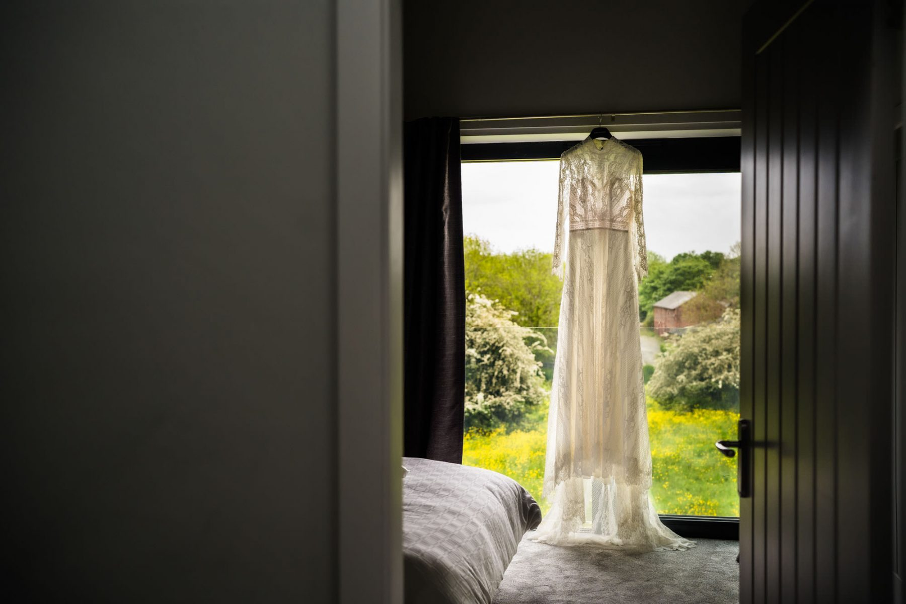 Wedding dress hanging with countryside in background